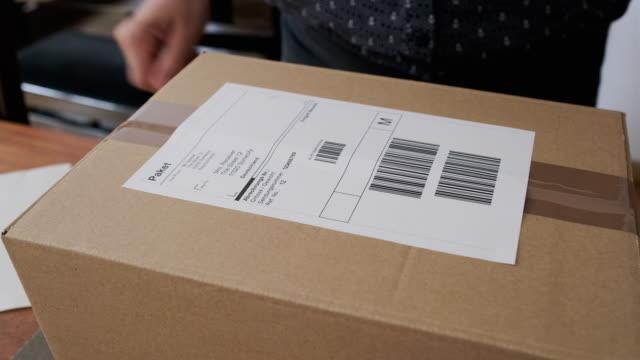 stockvideo's en b-roll-footage met vrouw die zaken van huis het etiketteren goederen in werking stelt - etiket