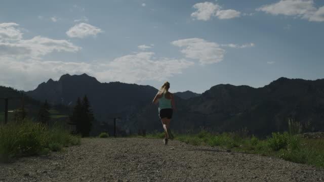vídeos y material grabado en eventos de stock de woman running down a trail - brighton ski area