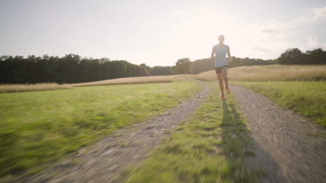 4K woman running fast behind camera in back light summer rural landscape