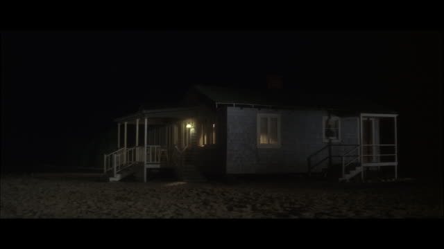 ms pan woman running from beach house at night  - beach house stock videos & royalty-free footage