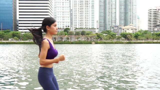 vídeos de stock, filmes e b-roll de mulher correndo em um parque, câmera lenta - sutiã para esportes