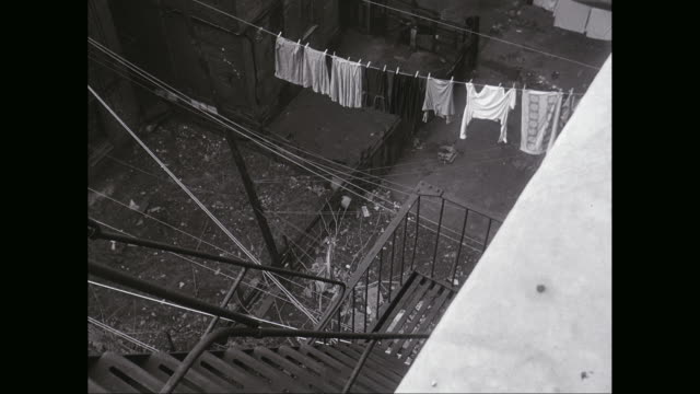 vídeos y material grabado en eventos de stock de ws ha woman running in alley between tenement buildings, clothes hanging on washing lines / united states - pinza de colgar la ropa