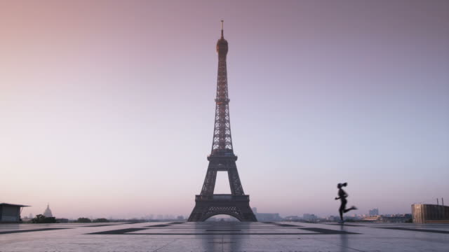 vidéos et rushes de woman running in front of the eiffel tower - jogging