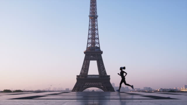 woman running in front of the eiffel tower - eiffel tower stock videos and b-roll footage