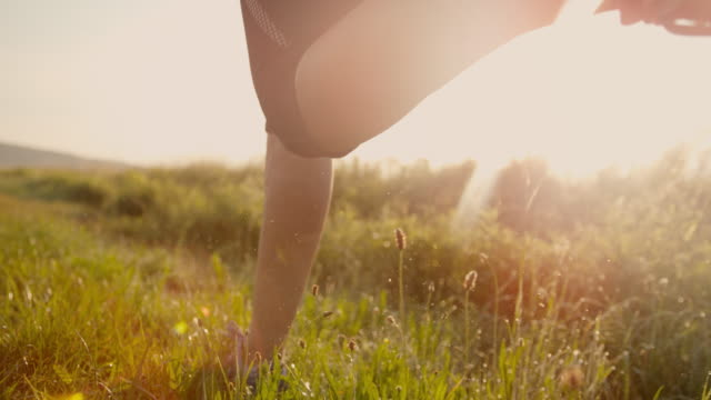 slo mo woman running in grass at sunset - human leg stock videos & royalty-free footage