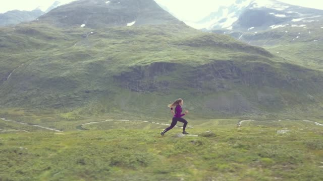 vidéos et rushes de woman running in high mountains, with beautiful view, aerial shot - veste et blouson