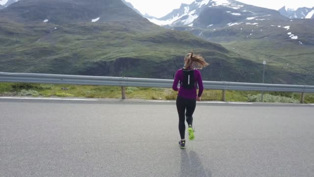 woman running in high mountains, with beautiful view, aerial shot - legging stock-videos und b-roll-filmmaterial