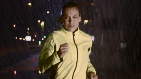 slo mo-ts frau laufen in der stadt bei nacht, bei regen - herausforderung stock-videos und b-roll-filmmaterial