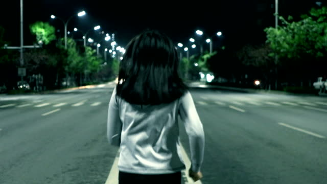 Woman running in the city street at night