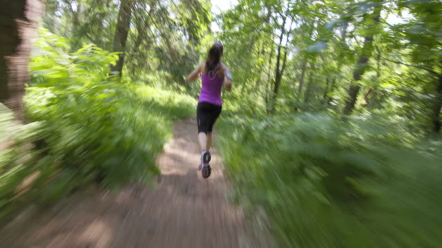 TS Woman running in the forest on a sunny day