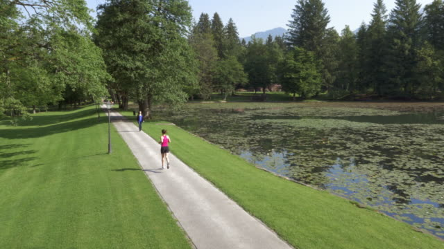AERIAL Woman running in the park along a lake
