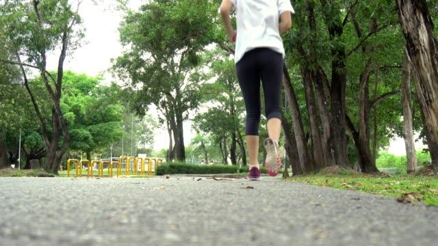 frau läuft in der straße am park - joggerin stock-videos und b-roll-filmmaterial