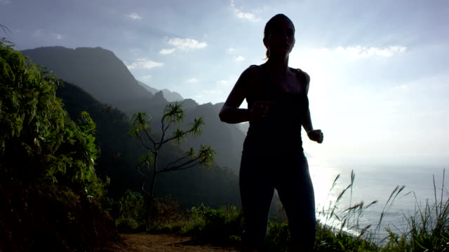 vídeos y material grabado en eventos de stock de mujer corriendo en tropical de hawai. - back lit