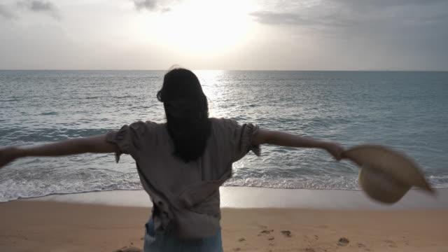 vídeos de stock, filmes e b-roll de mulher correndo na praia por do sol - mãos estendidas