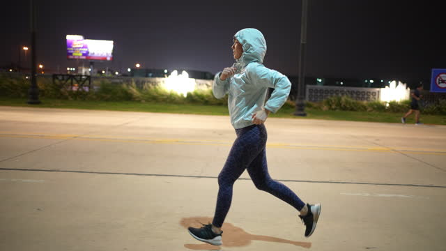 woman running jogging exercising in the night time - only teenage girls stock videos & royalty-free footage