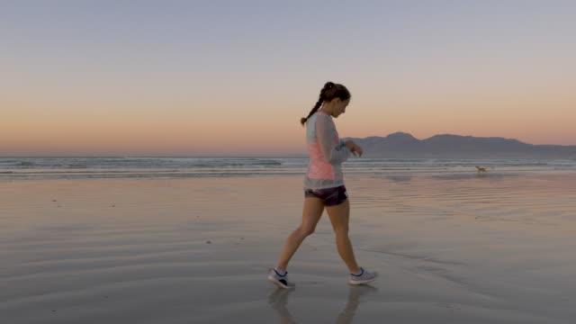 vídeos y material grabado en eventos de stock de woman running on a beach at dawn - corredora de footing