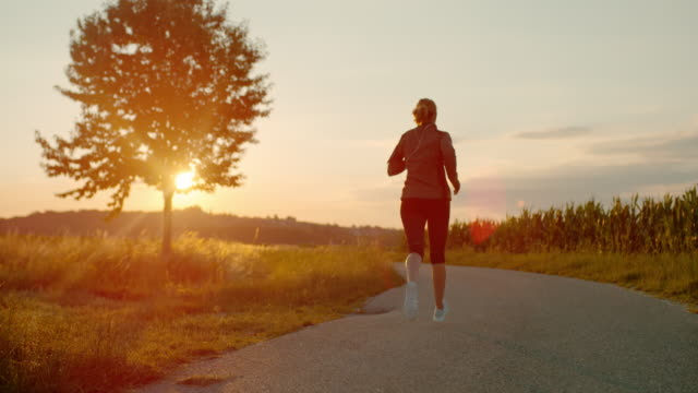slo mo woman running on a country road - alta sensibilità video stock e b–roll