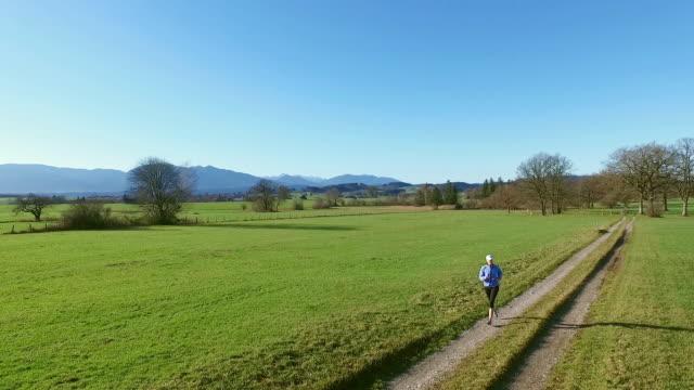 a woman running on a dirt road between green fields of grass - bayern stock-videos und b-roll-filmmaterial