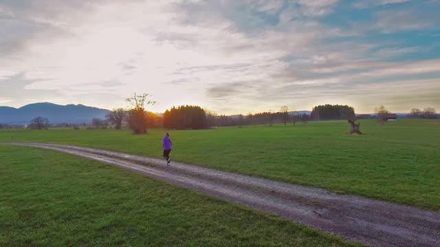 A woman running on a dirt road between green fields of grass