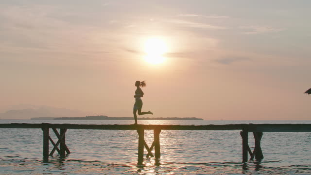 a woman running on a dock of a tropical island at sunset on a pier. - pier stock videos & royalty-free footage