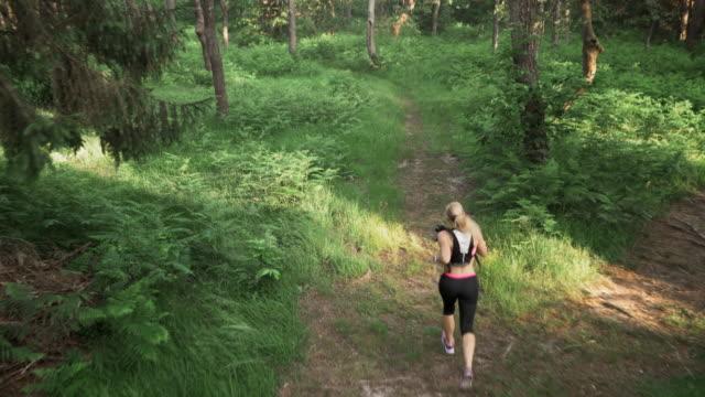 Luchtfoto vrouw draait op een pad door bos
