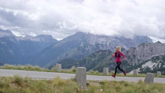 slo-mo-frau läuft auf eine straße hoch in den bergen mit einem wunderschönen blick - rucksack stock-videos und b-roll-filmmaterial