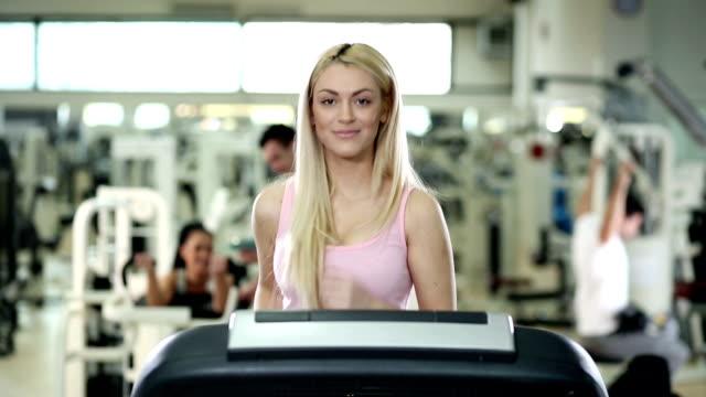 stockvideo's en b-roll-footage met woman running on a treadmill. - haar naar achteren