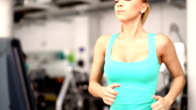 woman running on a treadmill. - sleeveless top stock videos & royalty-free footage