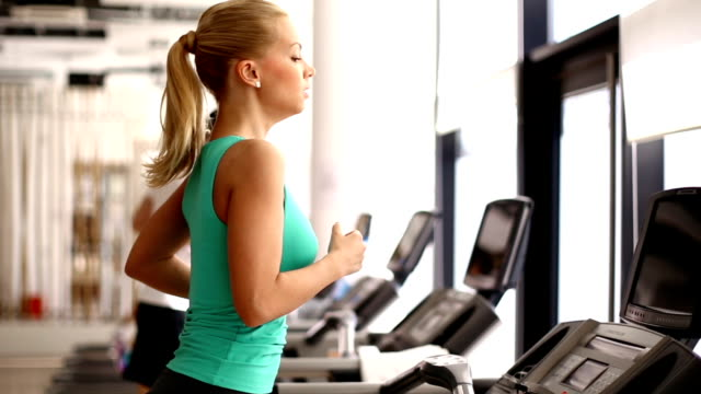 woman running on a treadmill. - brightly lit stock videos and b-roll footage