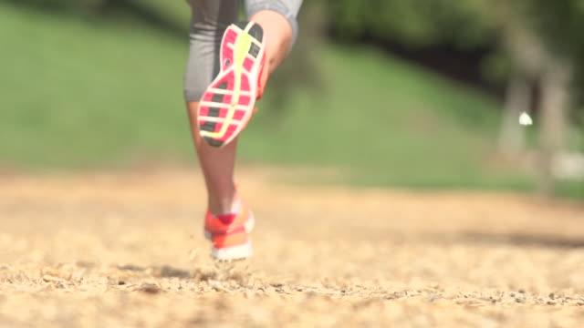 vídeos y material grabado en eventos de stock de a woman running on a wood chip trail. - slow motion - filmed at 240 fps - corredora de footing
