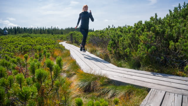 Woman running on a wooden pathway among pine bushes