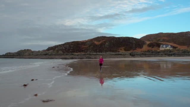 woman running on beach drone view - küste stock-videos und b-roll-filmmaterial