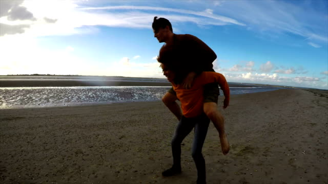 Woman running on beach with man on her back