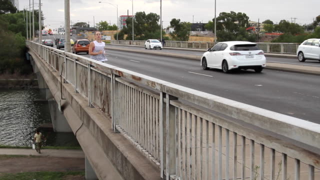 woman running on bridge alongside traffic - maglietta senza maniche video stock e b–roll