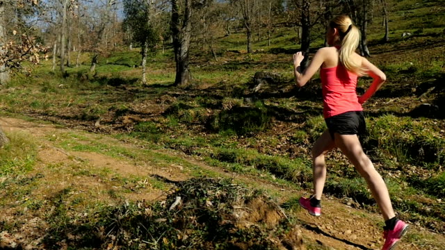 woman running on forest hill - running shorts stock videos and b-roll footage
