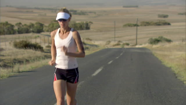 slo mo ts ws zi ms woman running on remote road with landscape in background / cape town, south africa - sun visor stock videos & royalty-free footage
