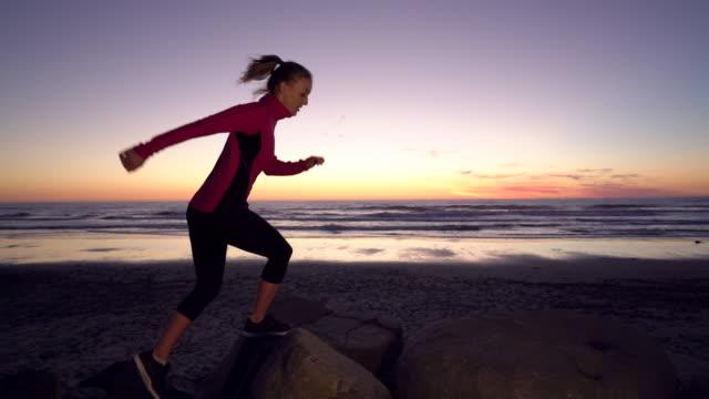 vidéos et rushes de ws sm ts woman running on rocks at sunset - seulement des jeunes femmes