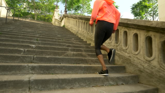 a woman running on stairs in a city for a workout. - slow motion - steps stock videos & royalty-free footage