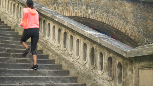A woman running on stairs in a city for a workout. - Slow Motion