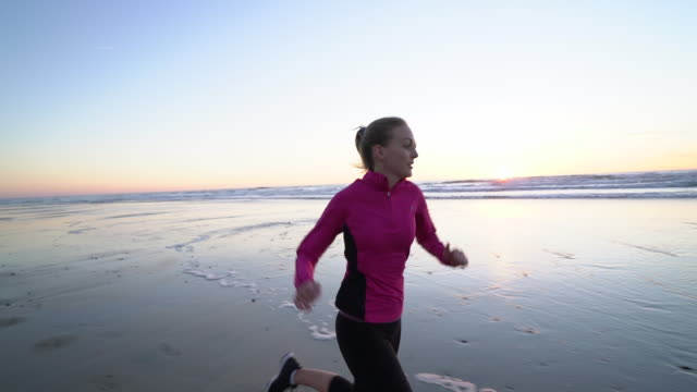 SM TS WS Woman running on the beach at sunset