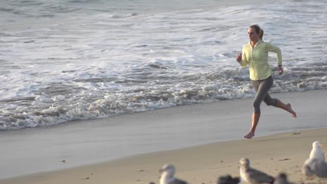 stockvideo's en b-roll-footage met a woman running on the beach. - slow motion - filmed at 240 fps - haar naar achteren
