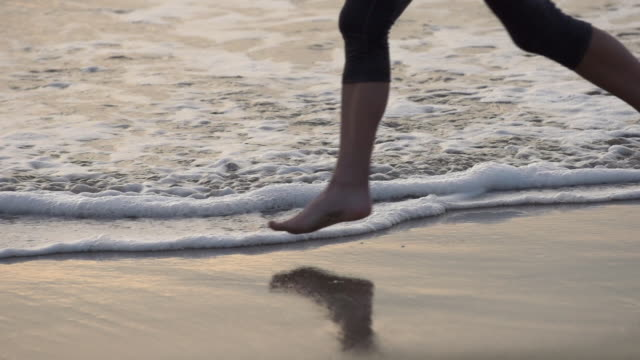 a woman running on the beach. - slow motion - filmed at 240 fps - barefoot点の映像素材/bロール
