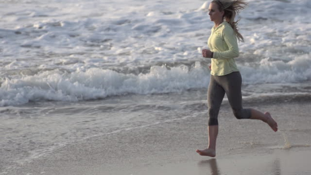 a woman running on the beach. - slow motion - filmed at 240 fps - 四匹点の映像素材/bロール