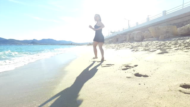 woman running on the beach. - black dress stock videos & royalty-free footage