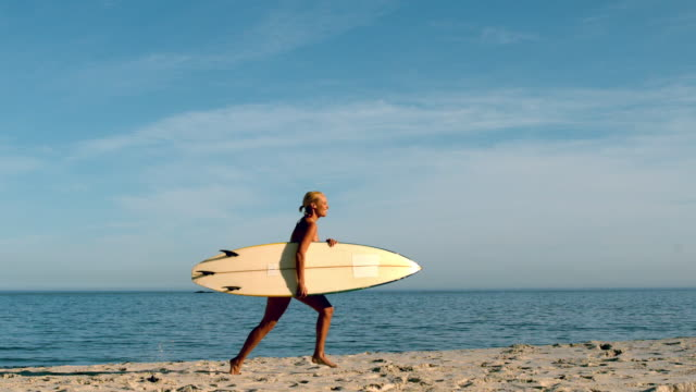 vídeos y material grabado en eventos de stock de woman running on the beach with her surfboard - tabla de surf