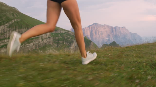 slo mo woman running on the top of a mountain ridge - human foot stock videos & royalty-free footage
