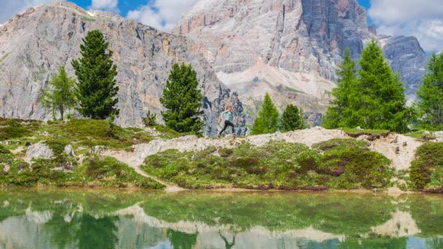 Frau läuft über Felsiges Gelände neben Bergsee