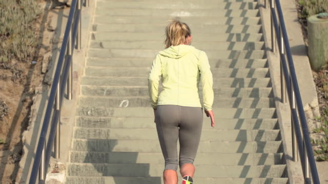 stockvideo's en b-roll-footage met a woman running stairs. - slow motion - filmed at 240 fps - haar naar achteren