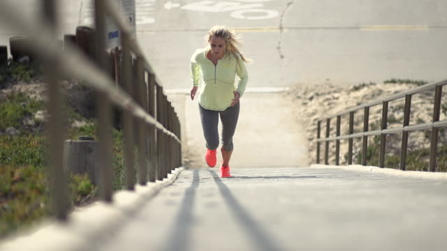 a woman running stairs. - slow motion - filmed at 240 fps - only young women stock videos and b-roll footage