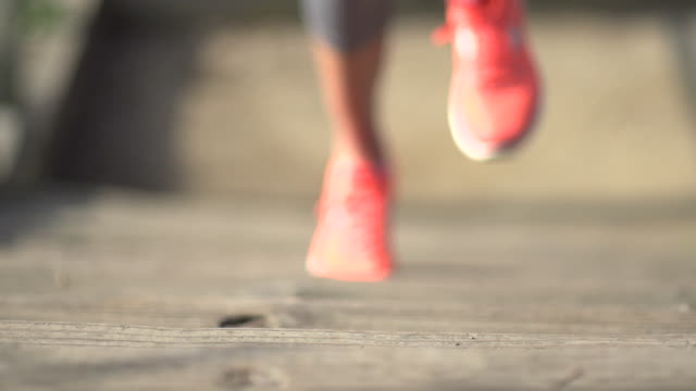 a woman running stairs. - slow motion - filmed at 240 fps - scarpe da ginnastica video stock e b–roll